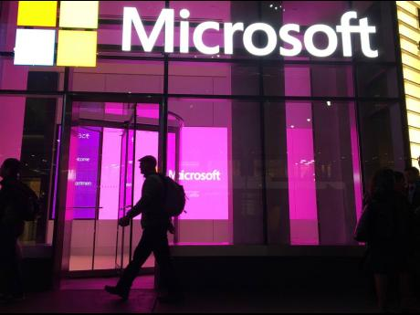 In this November 10, 2016 photo, people walk past a Microsoft office in New York.