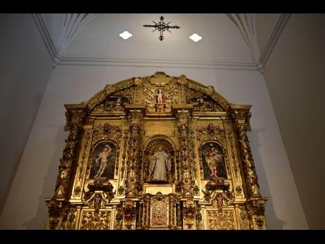 An altarpiece shows religious figures inside the second oldest Spanish church in the Americas, the San José Church, All the figures depicted on the church's gilded altar have been identified except for one: a woman with flaxen hair in the upper left-han