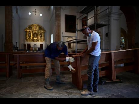 Workers set up a bench inside the San José Church. The church was built for a Dominican convent where the renowned Spanish priest Bartolomé de las Casas once lived.