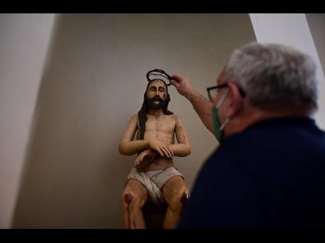 Architect Jorge Rigau arranges a crown of thorns on a statue of Jesus inside the San José Church.