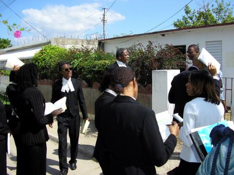 File  In this February 11, 2005 Gleaner photo, Justice Donald Mullings (third left), attorneys and court staff viewing Lot 1088, Fifth Seal Way in Braeton, St Catherine, where seven young men were killed by police on March 14, 2001.