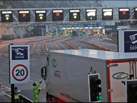 In this December 31, 2020 photo, lorries pass a checkpoint to embark by ferry to Europe, at the port in Dover, England.