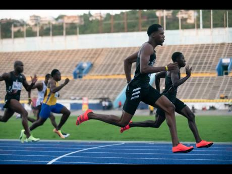Zharnel Hughes (foreground) wins the men's 100m event at the JAAA Qualification Trials 3.6 held at he National Stadium yesterday, in a time of 10.13 seconds. Oblique Seville (background), was second in 10.18 seconds.