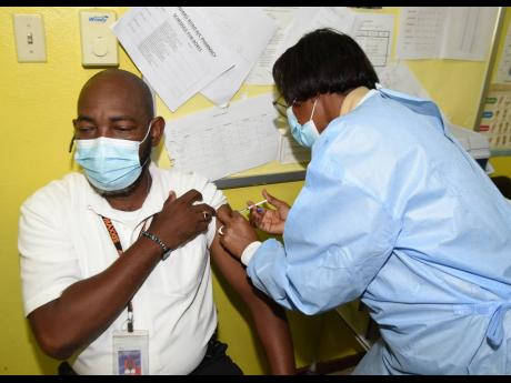 Public health driver Pietro Campbell from the Winward Road Health Centre receives his COVID-19 jab from public health nurse Lorraine Holt at the Kingston-based health centre yesterday.