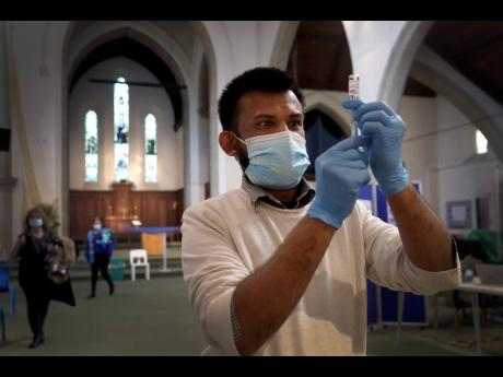 Pharmacist Rajan Shah prepares a syringe of the AstraZeneca vaccine at St John's Church, in Ealing, London, yesterday.