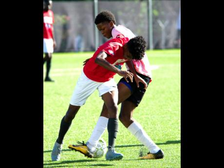 Alex Spencer (left) of Real Mona tries to get the better of Sean Porteous of Cavalier in their Alliance MoneyGram KSAFA Under-17 final, which was played at the UWI/JFF/Captain Horace Burrell Centre of Excellence on Saturday, July 13, 2019.