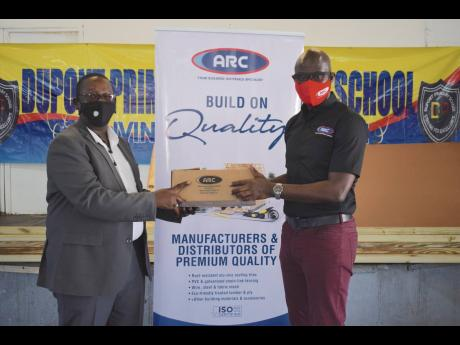 Principal of Dupont Primary & Infant School, Andrew Rowe (left), beams with joy as he receives a much-needed donation of building materials from ARC Manufacturing Limited's Managing Director, Deanall Barnes. The donation included an assortment of nails,