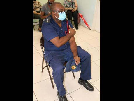 Assistant Superintendent Howard Thomas of the Jamaica Fire Brigade relaxes in the observation area after being vaccinated at The Good Samaritan Inn in Kingston on Wednesday.