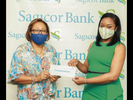 Terry-Ann Heffes (left), Sagicor Bank Jamaica client and one of three winners of the financial institution's recent credit card promotion, is presented with her hotel voucher for the all-expense paid three-night stay at Secrets Wild Orchid Resort in Mont