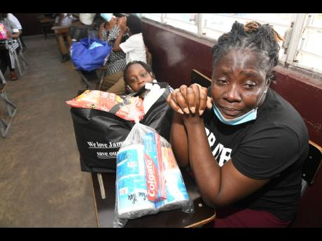 Francene Kelly (right), caregiver of Samara Davy (left), could not hold back the tears after expressing gratitude for the care package she received yesterday from the past students of the Elletson Primary and Infant School in Kingston. Care packages were g