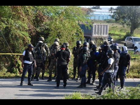 Policemen and soldiers gather to search a heavily vegetated section along the Spanish Town Bypass where four robbers who targeted a credit union in Portmore escaped after abandoning a Nissan Latio motor car.