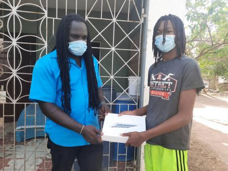 Otis James makes a donation of a tablet to Ayele Rodney, who has been out of school for seven months because he was without a tablet.