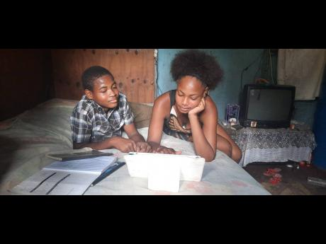 Tameka Brown logs on to classes using a tablet donated to her while he brother, Odanea Brown, looks on last Thursday. The boy has been without a device since last year and has not been attending school.