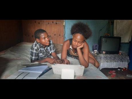Tameka Brown logs on to classes using a tablet donated to her while her brother, Odanea Brown, looks on last Thursday. The boy has been without a device since last year and has not been attending school.