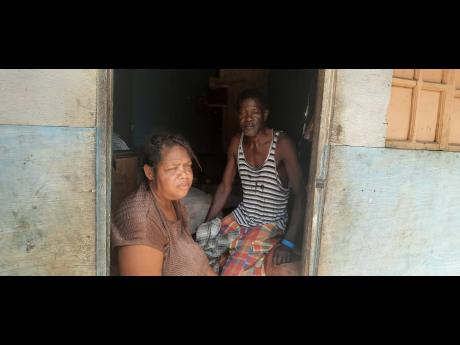 Parents Ann-Marie McKenzie and Cecil Brown look on despondently from their humble doorway as they outline economic challenges that have affected their ability to feed or send their children to school.