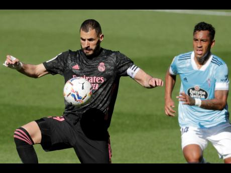 Real Madrid's Karim Benzema (left) controls the ball in front of Celta Vigo's Renato Tapia during a Spanish La Liga match between Celta and Real Madrid at the Balaidos stadium in Vigo, Spain, yesterday.