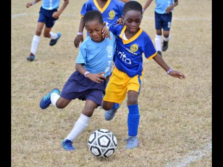 Jace Lowe (left) of Hillel Academy comes under pressure from Harbour View's JaQuaine Stewart during a match at the Victory Cup football tournament on February 22, 2020. Lowe scored all three goals as Hillel won the contest 3-2.