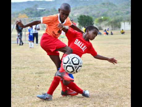Benders Football Club's forward Nicholas Ayre (left) tackles Malik Campbell of Ballaz Academy during their Under-9 match at the Victory Cup Football tournament. Benders won the game 1-0.