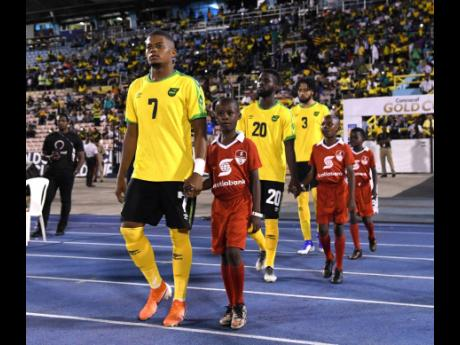 Leon Bailey and other members of Jamaica's national senior team make their way on to the field ahead of their Concacaf Gold Cup match against Honduras at the National Stadium on June 18, 2019.