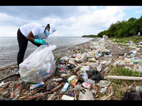 A volunteer from Recycling Partners of Jamaica picking up plastic bottles strewn along Sirganny Beach in East Kingston on Thursday, March 18.
