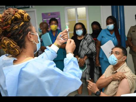 Prime Minister Andrew Holness watches as public health nurse Fiona Ellis gets ready to administer his first dose of the COVID-19 vaccine at the Good Samaritan Inn on Monday.