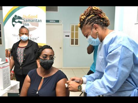 Juliet Holness, member of parliament for St Andrew East Rural and wife of Prime Minister Andrew Holness, gets her COVID-19 shot from public health nurse Fiona Ellis at the Good Samaritan Inn on Monday.