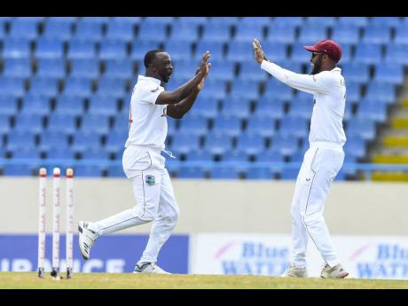 West Indies fast bowler Kemar Roach (left) celebrates with captain Kriagg Brathwaite after the dismissal of a Sri Lanka wicket during Day Three action of the first Test, which is being played at the Sir Vivian Richards Stadium in Antigua yesterday.