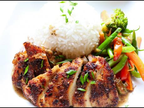 1. Pan-seared chicken topped with garlic-butter sauce is served with sautéed vegetables and jasmine rice.