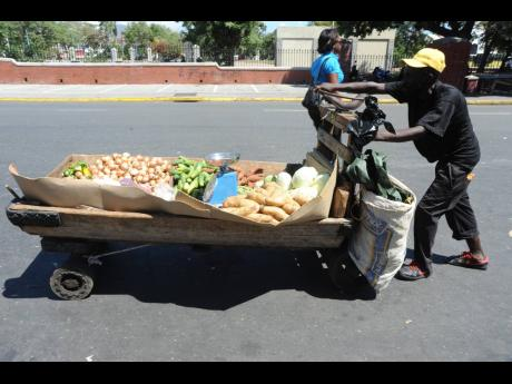In this 2014 file photo, a vendor pushes his handcart laden with produce in downtown Kingston.