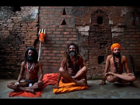 Indian Sadhus, or Hindu holy men, perform yoga on International Yoga Day at Kamakhya temple in Gauhati, India, Friday, June 21, 2019.