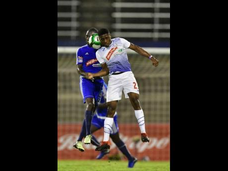 Mount Pleasant's Xavion Virgo (left) and Emelio Rousseau of Portmore United try to head the ball during a Jamaica Premier League semi-final at the National Stadium on Monday, April 15, 2019.