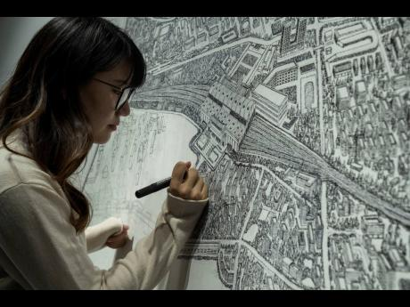 Chinese artist Yang Qian using dots to recreate an aerial view of Wuhan, China, under lockdown at her studio in Wuhan in central China's Hubei province.