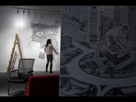 Chinese artist Yang Qian works on her art piece using pointillism to depict aerial views of Wuhan city during its 76-day lockdown in Wuhan in central China's Hubei province. Yang, who worked as a volunteer delivering vital supplies to hospitals and resid