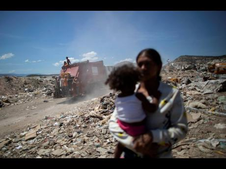 In this March 3, 2021 photo, youths who cull through trash for items to resell ride on the back of a garbage truck entering the Pavia landfill on the outskirts of Barquisimeto, Venezuela.