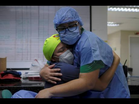 Health workers of the COVID-19 area embrace at the end of their shift at the Ana Francisca Perez de Leon II public Hospital in Caracas, Venezuela, on Tuesday, March 23.