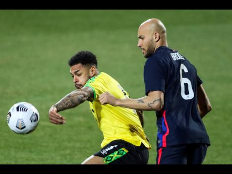 USA's John Brooks duels for the ball with Jamaica's Andre Gray (left) during their international friendly  match at SC Wiener  Neustadt stadium  in Wiener  Neustadt, Austria,  yesterday.