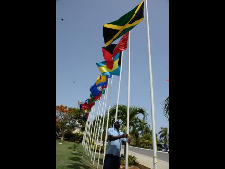 Brenton Hilton, groundsman at the Montego Bay Convention Centre in St James, making adjustments to the Jamaican flag in preparation for the CARICOM heads of government meeting on Wednesday, July 4, 2017.