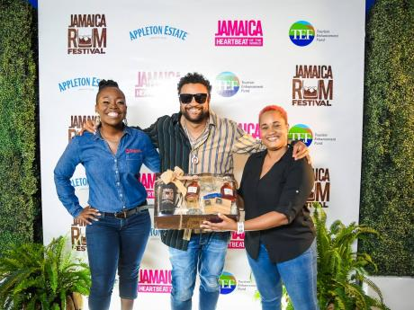 Reshima Kelly-Williams, brand marketing manager for Digicel Jamaica, stands with reggae and dancehall star Shaggy while he is being presented with a gift from Leleika-Dee Barnes, channel and customer marketing director, J. Wray and Nephew Limited.