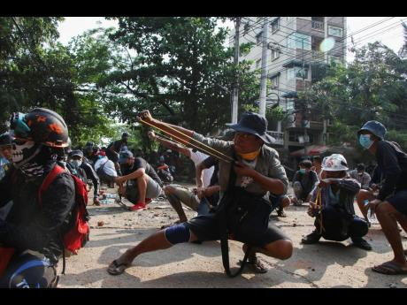 Anti-coup protesters use sling shot to confront police at Thaketa Township in Yangon, Myanmar on Sunday.