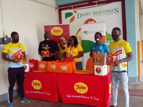 Dairy Industries present Tastee Cheese products to members of the Waterhouse Football club at Dairy Industries on Washington Boulevard in Kingston. From left are Waterhouse player Nicholay Finlayson, team manager Keith Salesman, Dairy Industries Brand Mana