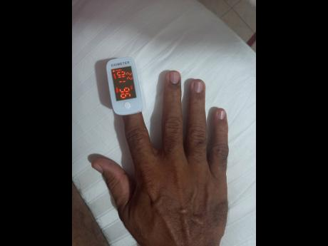Edward Chin-Mook checks a reading of his blood-oxygen level on an oximeter.