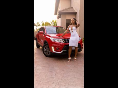 The birthday babe was not short on outfits, and this white number and its plunging bodice stands out perfectly against the red of the SUV.