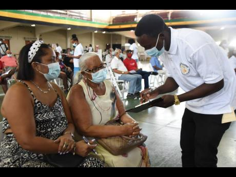 An employee of the public health department sensitising a senior citizen, who is among many who came to National Arena on Saturday, March 27, to get their first dose of AstraZeneca vaccine.