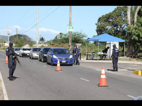 Police personnel man a checkpoint in Lionel Town, Clarendon, on Saturday. A 48-hour curfew imposed on the community last Friday lapsed Sunday evening.