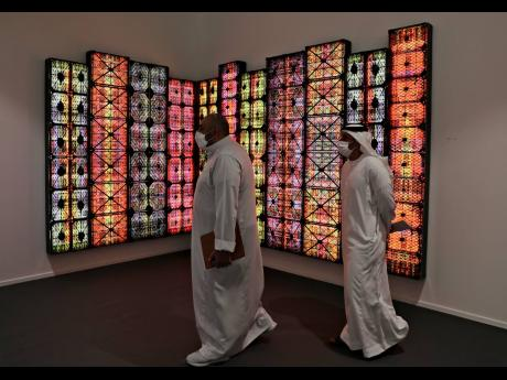 People visit Saudi artist Rashed Al Shashai's work titled Brand 14, Light Boxes, Plastic Cases, at the 14th edition of Art Dubai at Dubai International Financial Centre, DIFC, which features 50 galleries from 31 countries with a focus on modern and conte
