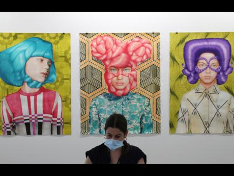 A gallery employee works in front of Angeles Agrela paintings at the 14th edition of Art Dubai at Dubai International Financial Centre, DIFC.