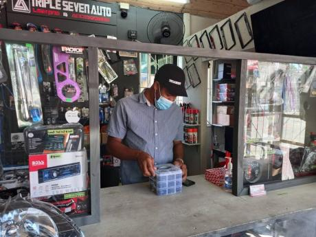 Donovan Cunningham, operator of Triple Seven Auto, Lighting and Accessories, examines a product before sale.