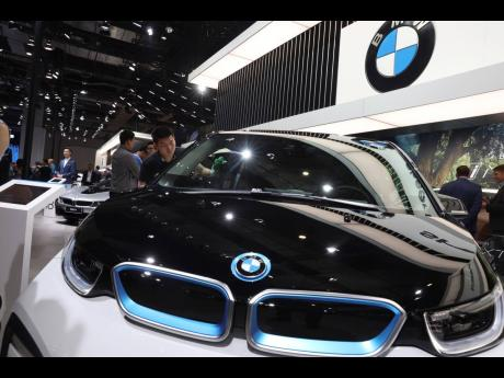 In this April 17, 2019 photo, a worker cleans an electric vehicle at the BMW booth during the Auto Shanghai 2019 show in China.