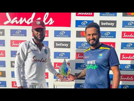 West Indies captain Kraigg Brathwaite (left) and his Sri Lankan counterpart Dimuth Karunaratne share the trophy for their two-match Test series that ended in a draw at the Sir Vivian Richards Stadium in North Sound, Antigua on Friday.