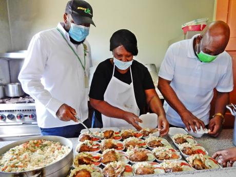 Mayor of  St Ann's Bay Sydney Stewart (right) and councillor for the Ocho Rios division and former mayor Michael Belnavis (left) help the cook at the Ocho Rios drip-in centre, Lorna Douglas, to share lunches for street people on Good Friday.